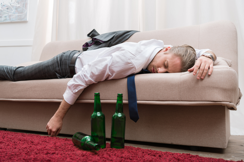 drunk man sleeping on couch
